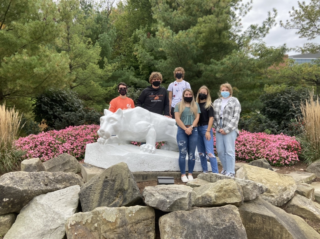 A group of students posing in front of the Nittany Lion at Penn State Behrend Campus