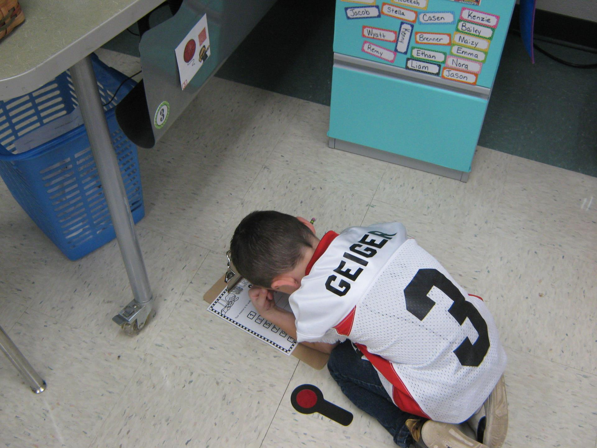 Student recording his discovery on a clipboard.  His magnifying glass is laying on the floor next to him.