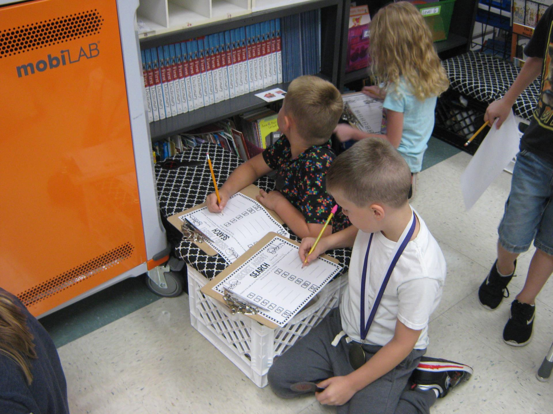 Students record their discoveries on their clipboards.  They are seated on the floor next to the book case.