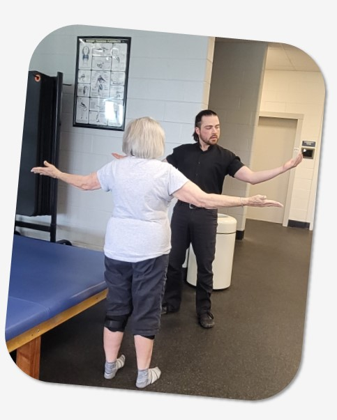 personal trainer and Y member raising arms