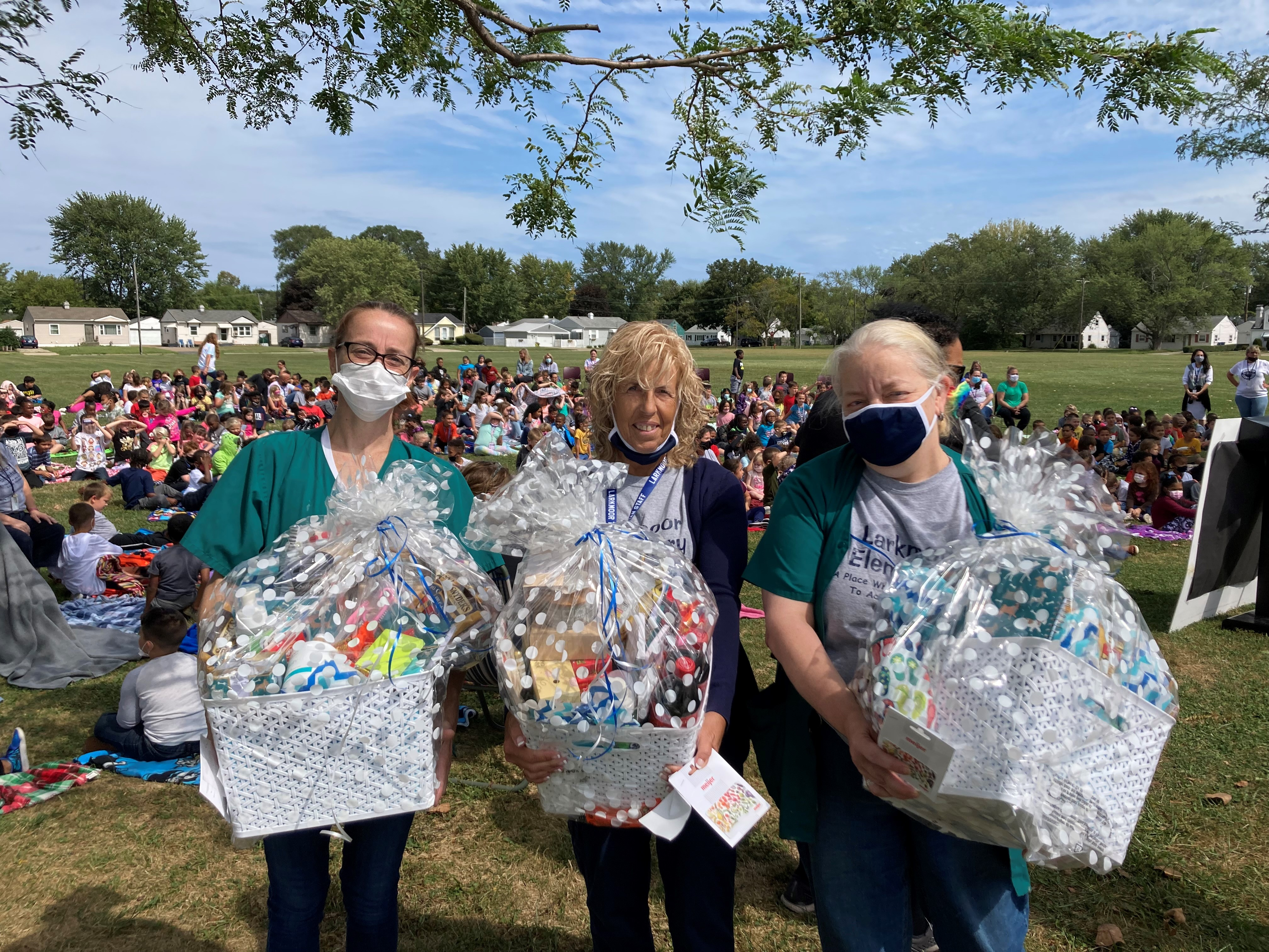 Three Larkmoor Elementary School staff members hold gift baskets and gift card from Meijer, which recognized the staff members on Wednesday, September 15, 2021